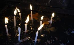 Weiße Kerzen des Lit mit geschmolzenem Wachs auf dunkler Wasseroberfläche Stockfotografie