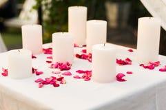 Weiße Kerzen umgeben mit den rosa rosafarbenen Blumenblättern Stockfoto