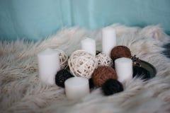 weiße Kerzen und Dekoreinzelteile auf weißem Teppich stockbild