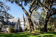 Weiße Kirche unter spanischem Moos und grünem Rasen Stockbilder