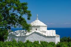 Weiße Kirche vor dem blauen Meer, gestaltet durch Büsche und einen Baum, Samos, Griechenland stockbild