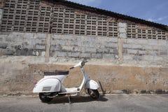 Weiße klassische Vesparollerstände parkten nahe dem alten Beton Lizenzfreie Stockfotos