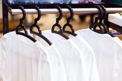 Weiße Kleidung, die an den Aufhängern in einem Speicher hängt Stockbild