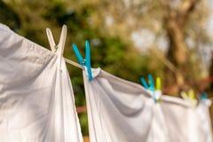 Weiße Kleidung hing heraus, um auf einer waschenden Linie zu trocknen und befestigt durch die Kleiderhaken am hellen warmen sonni lizenzfreie stockfotografie