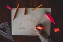Weiße kleine Hände einer kaukasischen Kleinkindkinderzeichnung mit einem orange Bleistift auf Papier lizenzfreie stockfotografie