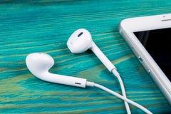 Weiße kleine Kopfhörer und weißer Smartphone auf einem blauen rustikalen Holztisch Woodgrain-Beschaffenheit lizenzfreie stockfotografie