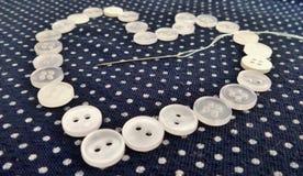 Weiße Knöpfe Valentine Hearts und Threadnadel auf blauem und weißem Tupfenstoff Lizenzfreie Stockfotos