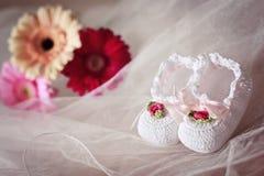 Weiße Knitbabybeuten verziert mit Blumen Lizenzfreie Stockfotos