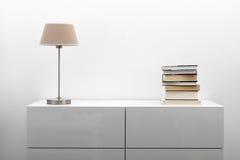 Weiße Kommode mit Lampe und Büchern im hellen Innenraum Stockbild