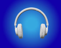 Weiße Kopfhörer auf blauem Scheinwerferhintergrund Lizenzfreie Stockfotos