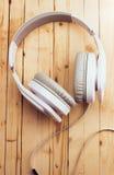 Weiße Kopfhörer auf einem hölzernen Hintergrund Stockbilder