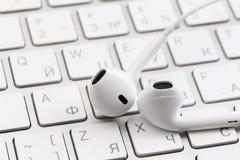 Weiße Kopfhörer auf weißer Tastatur lizenzfreie stockbilder