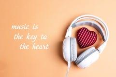 Weiße Kopfhörer mit Rot strickten Herz und Phrase Musik ist stockfotografie