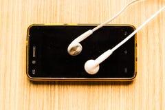 Weiße Kopfhörer am schwarzen Telefon lizenzfreie stockfotos
