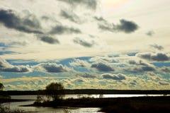 Weiße Kumuluswolken im blauen Himmel, Nacht, natürlicher Hintergrund, Himmel, Tag, Wolken, Wasser, See, Teich, Bäume, Wald, Kirch lizenzfreie stockfotos