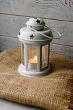 Weiße Laterne mit einer brennenden Kerze nahe bei einer Geschenkbox Lizenzfreie Stockfotos