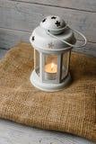Weiße Laterne mit einer brennenden Kerze nahe bei einer Geschenkbox Stockbilder
