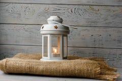 Weiße Laterne mit einer brennenden Kerze nahe bei einer Geschenkbox Stockfoto