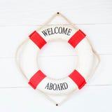 Weiße Lebenboje mit Willkommen an Bord auf weißer Wand Stockfotografie
