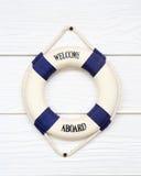 Weiße Lebenboje mit Willkommen an Bord auf weißer Wand Lizenzfreies Stockbild