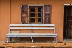 Weiße leere Bank auf einem hölzernen Fenster und einer orange Wand Stockfotos