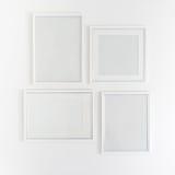 Weiße leere Bilderrahmen, die am Weiß hängen Stockbild