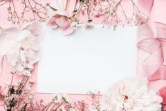 Weiße leere Karte mit Pastellblumen und Band auf rosa blassem Hintergrund, Blumenrahmen Kreativer Gruß, Einladung Stockfotos