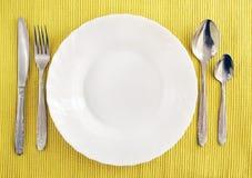 Weiße leere Platte mit Gabel, Löffel und Messer Lizenzfreie Stockfotografie
