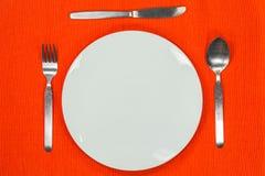 Weiße leere Platte mit Gabel, Löffel und Messer Lizenzfreies Stockfoto