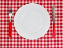 Weiße leere saubere Platte auf rotem Tischdeckenhintergrund mit dishwa Lizenzfreie Stockfotografie