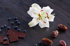 Weiße Lilie mit Früchten und Schokolade Lizenzfreies Stockfoto