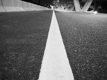 Weiße Linie auf Asphaltstraße in der Schwarzweiss-Farbe Stockfotos