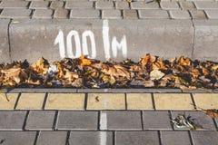 Weiße Linie und Zahlen gemalt auf Bürgersteig und Beschränkung Stockfotos