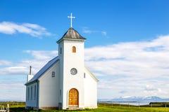 Weiße lutherische Kirche Flateyjarkirkja mit Wiese im Vordergrund lizenzfreie stockbilder