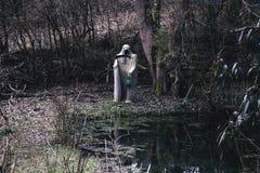 Weiße Mähmaschine des Todes mit gespenstischer Sense und Lampe in einem kleinen Teich stockfotografie