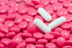 Weiße medizinische Kapseln auf rotem backgro Pillen des viel Stockfotografie