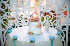 Weiße mehrstufige Hochzeitstorte verziert mit rosa Sahneblumen auf weißer Tabelle Schokoriegelkonzept Stockbild