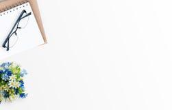 Weiße minimale Schreibtischtabelle mit Notizbuch, Gläsern und Blume Lizenzfreie Stockfotos