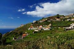 Weiße Mittelmeerhäuser auf einem steilen Abhang umgeben durch Bananenplantagen Stockfotografie