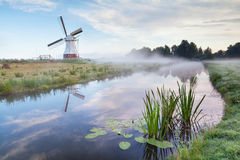 Weiße niederländische Windmühle am nebelhaften Morgen Lizenzfreies Stockfoto