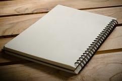 Weiße Notizbücher, die auf einen Holztisch legen Lizenzfreie Stockfotografie
