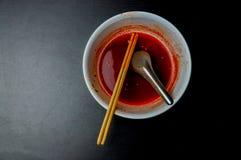 Weiße Nudelschüssel mit roter würziger Suppe stockfotos
