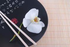 Weiße Orchidee auf einer schwarzen Platte Lizenzfreie Stockbilder