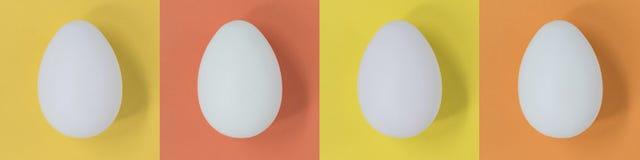 Weiße Ostereier auf einer Fahne mit Pastellmehrfarbenquadraten lizenzfreies stockbild