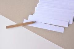 Weiße Papierstreifen für Anmerkungen mit Bleistift auf einem Papierhintergrund Lizenzfreie Stockfotos