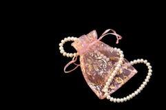 Weiße Perlen in der Spitzen- Handtasche auf der schwarzen Seide lizenzfreies stockbild