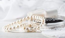 Weiße Perlenhalskette, das Zubehör der Frauen, auf handgemachter Spitzerückseite Stockbilder