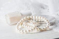 Weiße Perlenhalskette, das Zubehör der Frauen, auf handgemachter Spitzerückseite Stockfotos