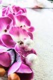 Weiße Perlenohrringe handgemacht nahe bei bunten Blumen in einem hellen Licht Lizenzfreie Stockfotografie