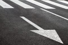 Weiße Pfeile und Zebrastreifen auf der Straße Stockfotos